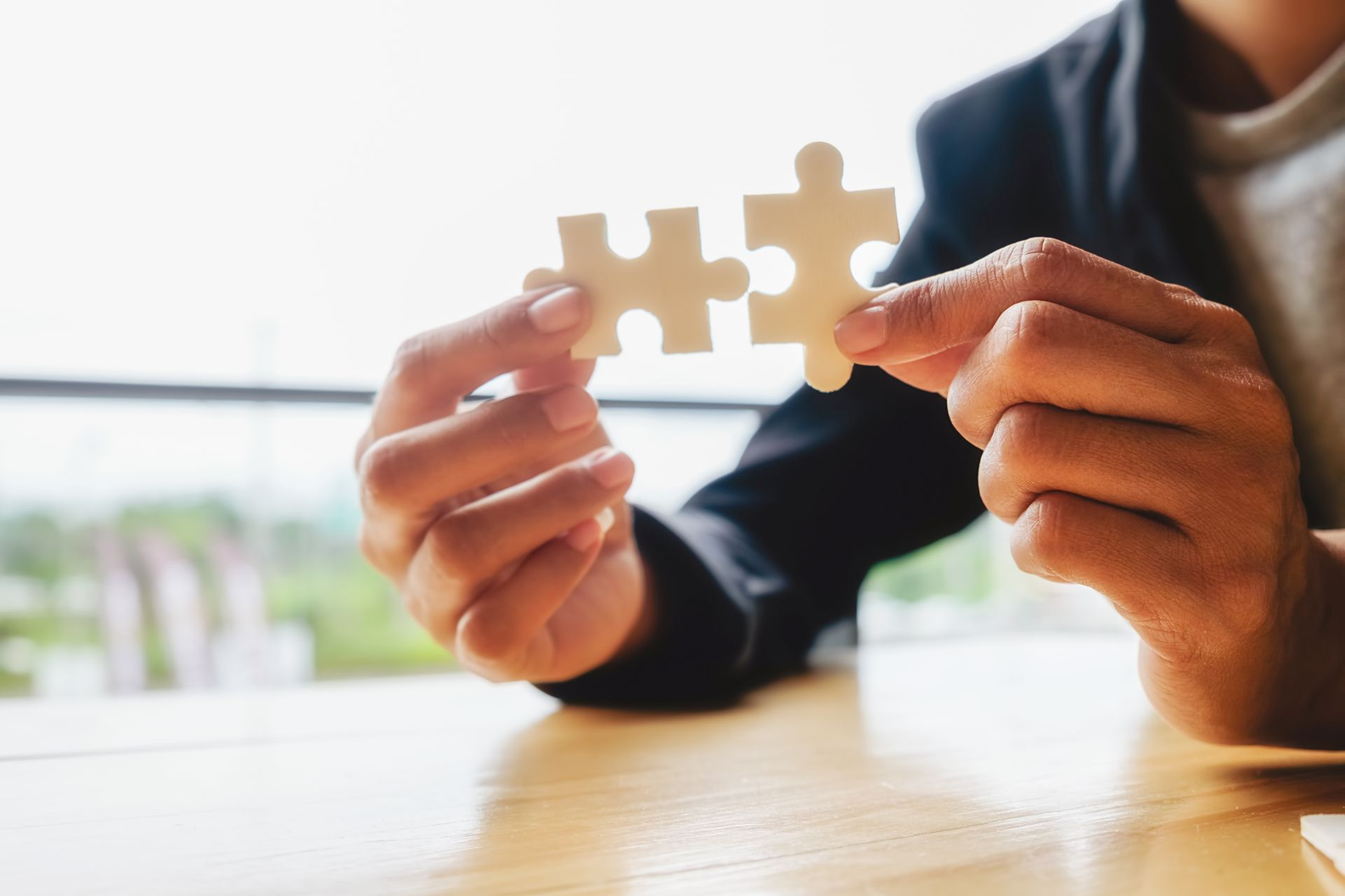 Business woman hands connecting jigsaw puzzle. Business solutions, success and strategy concept. Businessman hand connecting jigsaw puzzle.Close up photo with selective focus.