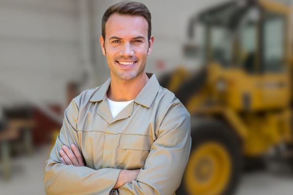 Male worker standing with arms crossed against blurr background